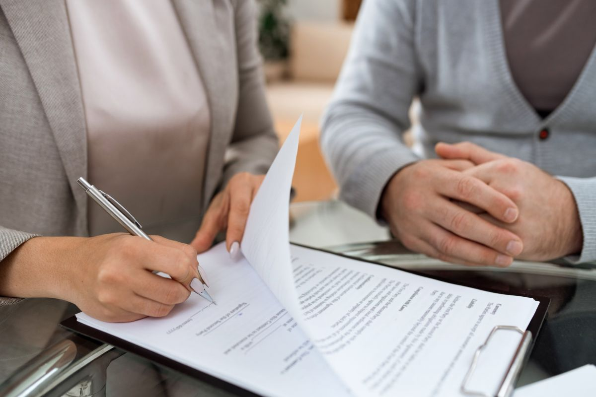 One of business partners putting signature on last page of financial contract