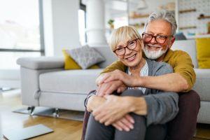 Happy romantic senior couple hugging and enjoying retirement at home